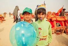 Enfants heureux ayant l'amusement sur le carnaval de désert pendant le festival de désert dans l'Inde Photographie stock