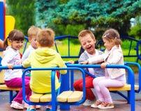 Enfants heureux ayant l'amusement sur le rond point au terrain de jeu Image libre de droits