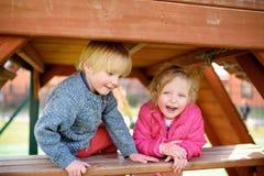 Enfants heureux ayant l'amusement sur le terrain de jeu extérieur Images stock