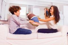 Enfants heureux ayant le combat d'oreiller pour l'amusement sur le sofa Image libre de droits