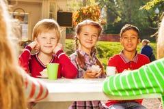 Enfants heureux buvant du thé avec se reposer de petits gâteaux Photographie stock