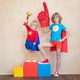 Enfants heureux conduisant la voiture de jouet à la maison photos libres de droits