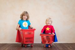 Enfants heureux conduisant la voiture de jouet à la maison images libres de droits