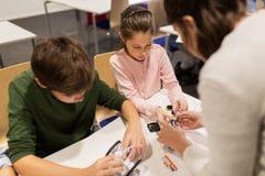 Enfants heureux construisant des robots à l'école de robotique Images stock