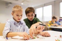 Enfants heureux construisant des robots à l'école de robotique Image stock