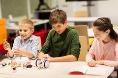 Enfants heureux construisant des robots à l'école de robotique Photographie stock
