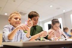 Enfants heureux construisant des robots à l'école de robotique Photographie stock libre de droits