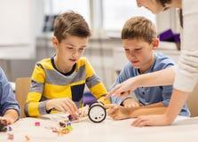 Enfants heureux construisant le robot à l'école de robotique Photographie stock