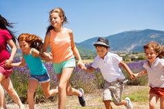 Enfants heureux courant ensemble dans des domaines de lavande Photographie stock libre de droits