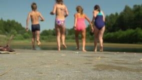 Enfants heureux courant et sautant dans l'eau d'un pilier banque de vidéos