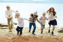 Enfants heureux courant par le lac Photographie stock libre de droits