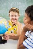 Enfants heureux d'école avec le globe dans la salle de classe images stock