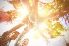 Enfants heureux d'école formant la pile de main Image libre de droits