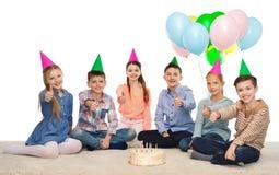 Enfants heureux dans des chapeaux de partie avec le gâteau d'anniversaire Photographie stock libre de droits