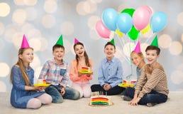 Enfants heureux dans des chapeaux de partie avec le gâteau d'anniversaire Photos stock