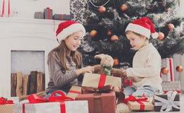 Enfants heureux dans des chapeaux de Santa déroulant des cadeaux de Noël photos libres de droits