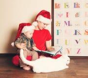 Enfants heureux dans des chapeaux de Santa lisant un livre de Noël Grand bouillon Image libre de droits