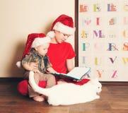 Enfants heureux dans des chapeaux de Santa lisant un livre de Noël Grand bouillon Images stock
