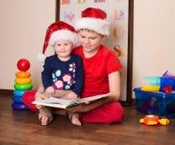 Enfants heureux dans des chapeaux de Santa lisant un livre de Noël Grand bouillon Photo stock