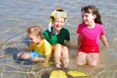 Enfants heureux dans l'eau Photos stock
