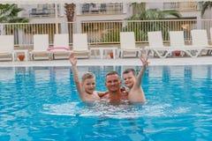 Enfants heureux dans la piscine avec son père des vacances image libre de droits