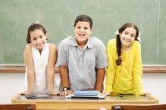 Enfants heureux dans la salle de classe Photos stock