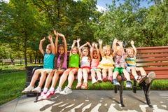 Enfants heureux dans le banc de parc Photographie stock
