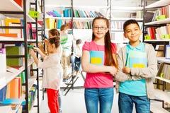 Enfants heureux dans le support de bibliothèque ainsi que des livres Photographie stock libre de droits