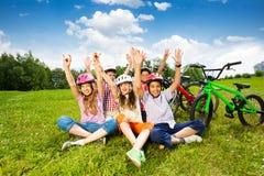 Enfants heureux dans les casques sur l'herbe avec des mains  Image stock