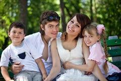 Enfants heureux de famille et de groupe sur le banc en stationnement. Photos libres de droits