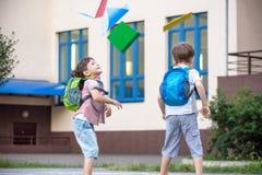 Enfants heureux - deux amis avec des livres et des sacs à dos sur le Th Image libre de droits