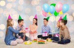 Enfants heureux donnant des présents à la fête d'anniversaire Photographie stock