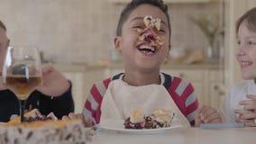 Enfants heureux dupant autour tout en mangeant le gâteau Les enfants rient Garçon d'afro-américain avec un visage sali dans a banque de vidéos