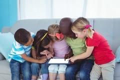 Enfants heureux employant la technologie tout en se reposant Photos stock
