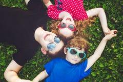 Enfants heureux en verres se trouvant sur l'herbe Conce heureux de famille Image stock