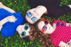 Enfants heureux en verres se trouvant sur l'herbe Conce heureux de famille Image libre de droits