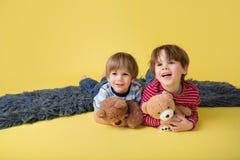Enfants heureux, enfants de mêmes parents, étreignant les jouets bourrés Images stock