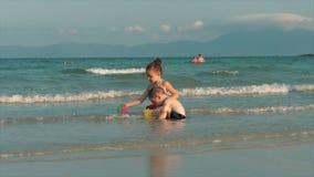 Enfants heureux et insouciants jouant par la mer avec le sable Jeu de jeu d'enfants, de frère et de soeur par la mer heureux banque de vidéos