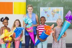 Enfants heureux et professeur tenant des cadeaux dans la salle de classe images stock