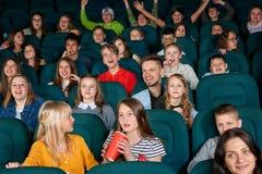 Enfants heureux et sortis s'asseyant dans le cinéma Images stock