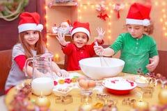 Enfants heureux faisant des biscuits Photographie stock libre de droits