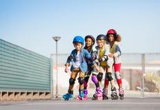Enfants heureux faisant du roller dans une rangée dehors Photos stock