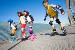 Enfants heureux faisant du roller sur la route au jour ensoleillé Photos libres de droits