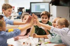Enfants heureux faisant la haute cinq à l'école de robotique Images stock