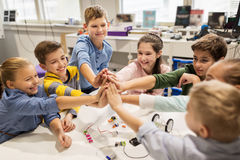Enfants heureux faisant la haute cinq à l'école de robotique Photos stock