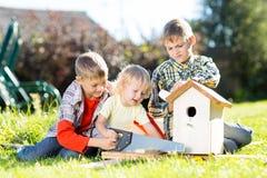 Enfants heureux faisant la volière en bois à la main Un enfant plus âgé enseigne son jeune frère Photo libre de droits