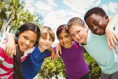 Enfants heureux formant le petit groupe au parc Photos stock