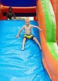 Enfants heureux glissant en bas d'une maison gonflable de rebond Image stock