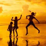 Enfants heureux jouant à la plage Photos libres de droits
