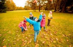 Enfants heureux jouant avec des feuilles d'automne en parc Photographie stock